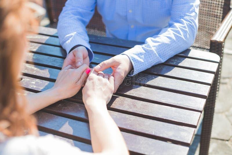 Hände des Mannes und der Frau angeschlossen auf Tabelle, Ansicht von oben Sie sitzen bei Tisch Warteauftrag und betrachten stockbild