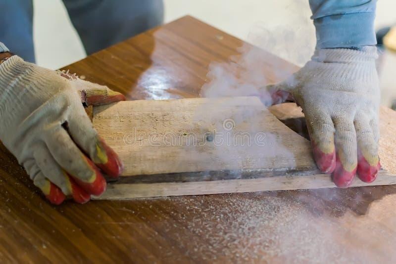 Hände des Meisters in den Handschuhen halten ein hölzernes Billet lizenzfreies stockbild
