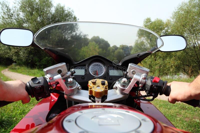 Hände des Motorradfahrers auf Landstraße lizenzfreies stockfoto