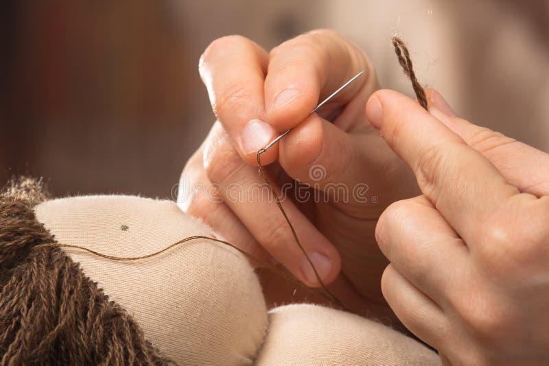 Hände des nähenden Haares der Frau zur Waldorf-Puppe lizenzfreie stockfotos