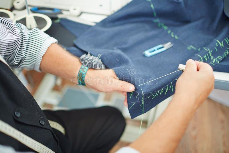 Hände des nähenden Kleides des Schneiders lizenzfreie stockbilder