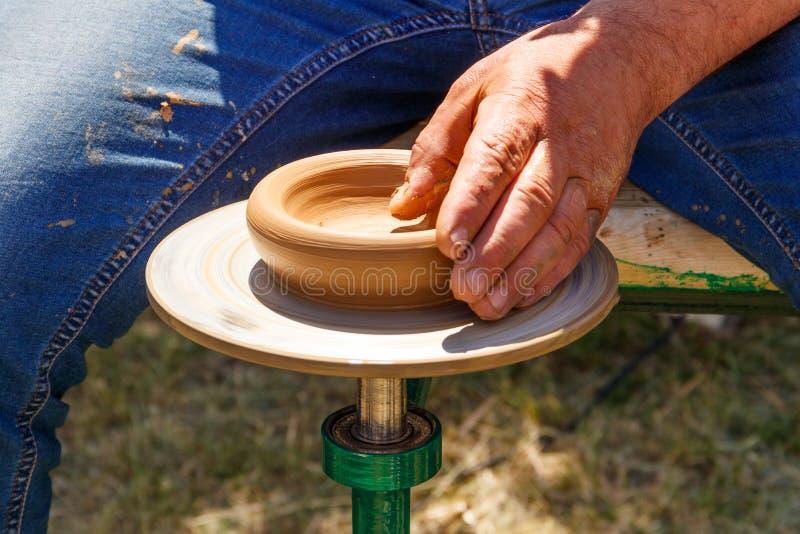 Hände des reifen Mannes Tonwaren auf Töpferscheibe machend Nahaufnahme stockfoto