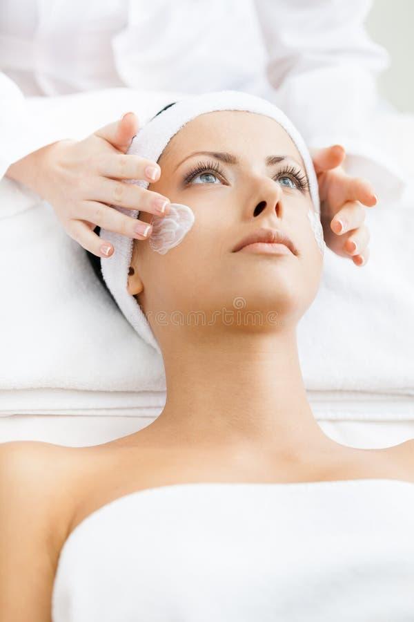 Hände des Therapeuten tragen Creme am Frauengesicht auf stockfotografie