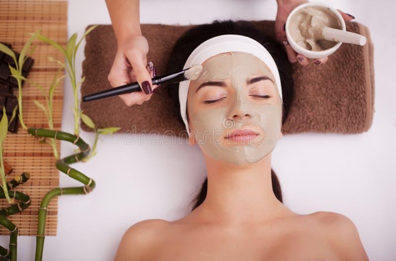 Hände des Therapeuten tragen Creme am Gesicht der Frau auf Konzept von Sorgfalt und von Jugend lizenzfreie stockbilder