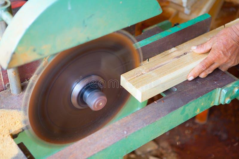 Hände des Tischlers oder des Handwerkers schnitten ein Stück Holz zu Machi lizenzfreie stockbilder