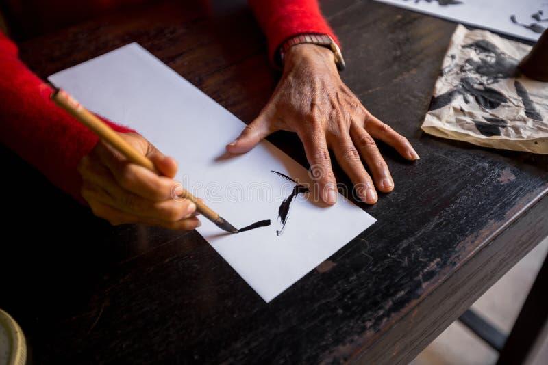 Hände des traditionellen Schreibkünstlers in Hoi An lizenzfreies stockfoto