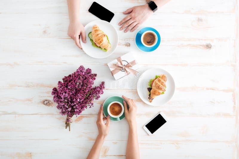 Hände des trinkenden Kaffees der Paare und der essen Hörnchen auf Tabelle lizenzfreie stockbilder