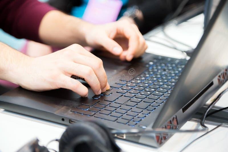 Hände des unrecognisable geernteten jungen Mannes, der auf Laptop-Computer schreibt lizenzfreie stockbilder