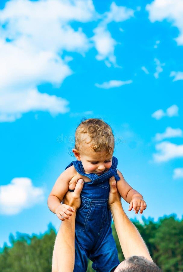 Hände des Vaters herauf seinen kleinen Sohn zum Himmel stockfotografie