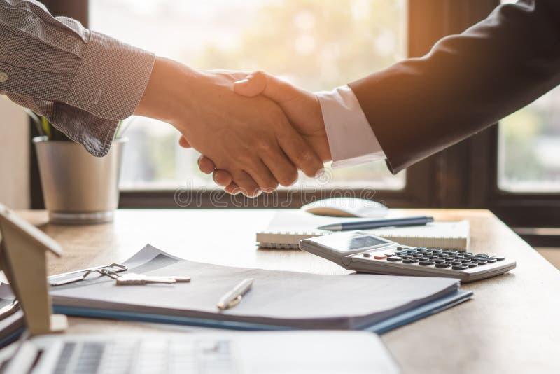 Hände des Vertreters und des Kunden, die Hände nach unterzeichneter neuer Wohnung des Vertragskaufes rütteln stockfotografie