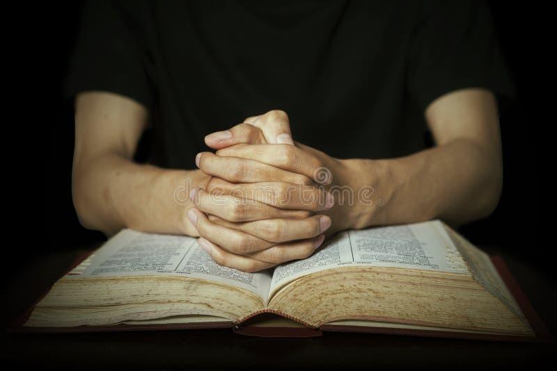 Hände, die auf Bibel beten lizenzfreie stockfotografie