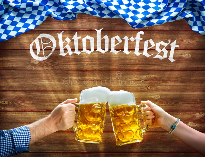 Hände, die Bierkrüge unter bayerischer Flagge halten lizenzfreie stockbilder