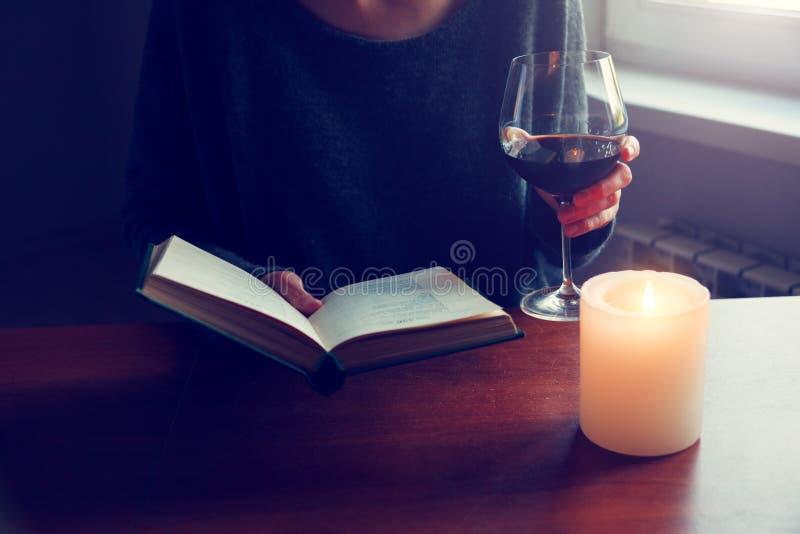 Hände, die Buch halten und mit Wein lesen lizenzfreie stockbilder