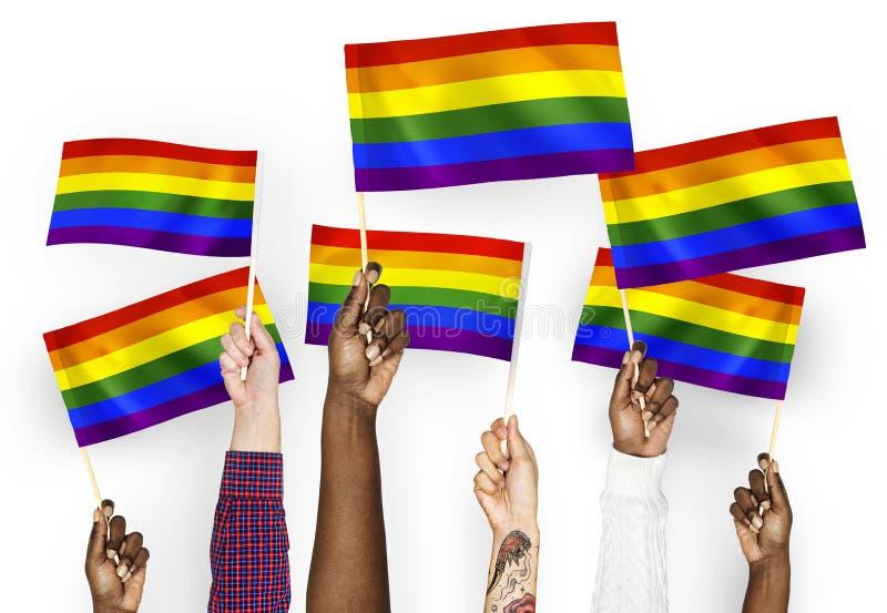 Hände, die bunte Regenbogenflaggen wellenartig bewegen lizenzfreie stockbilder