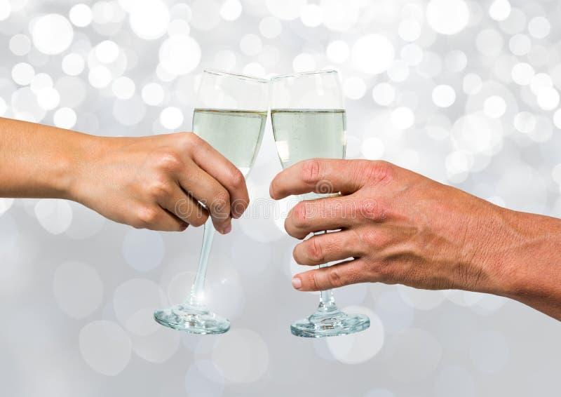 Hände, die Champagner mit funkelndem hellem bokeh Hintergrund halten lizenzfreie stockfotografie