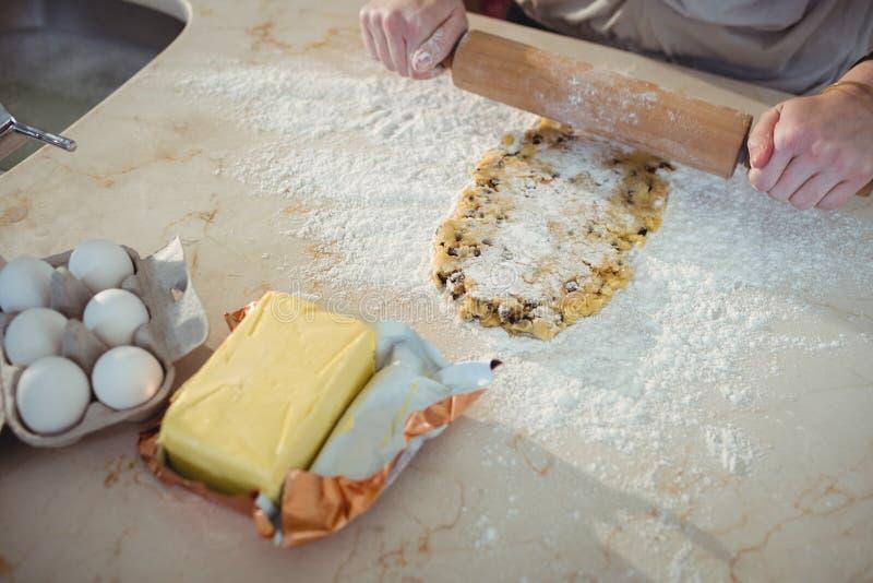 Hände, die den Teig mit Nudelholz in der Küche bedecken stockfotografie