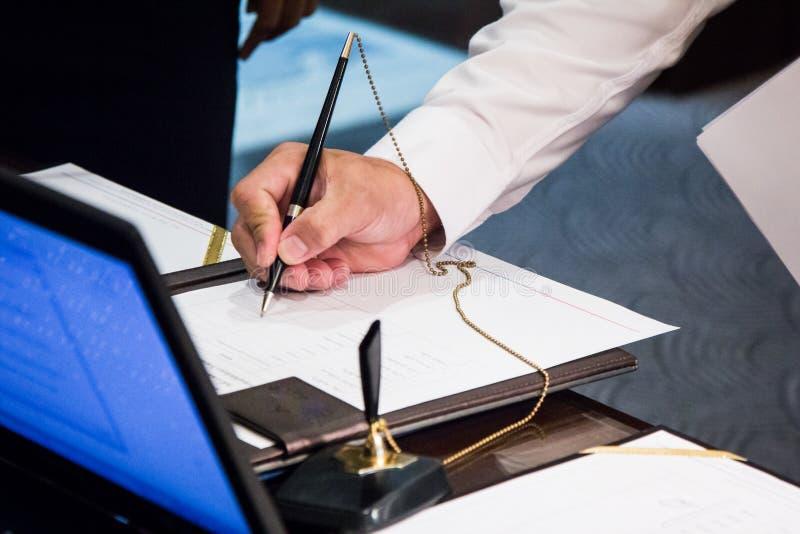 Hände, die an der Geschäftsunterzeichnung schreiben lizenzfreies stockfoto
