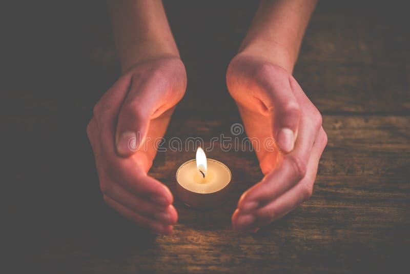 Hände, die die Flamme schützen stockbild