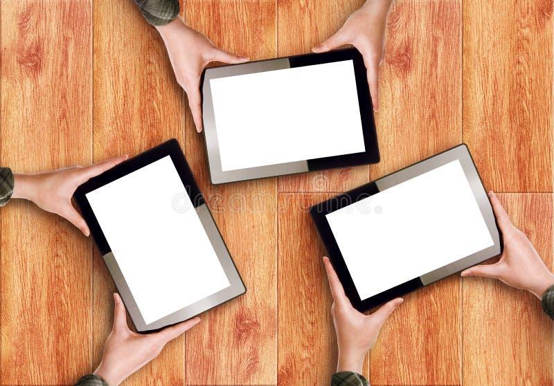 Hände, die drei Digital-Tablet-Computer halten stockfotografie