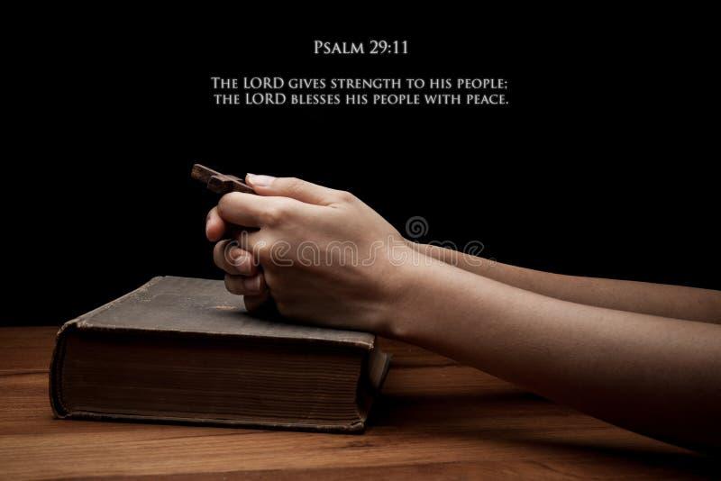 Hände, die ein Kreuz auf heiliger Bibel mit Vers halten stockfotografie