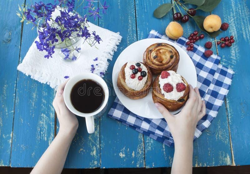 Hände, die eine blaue Schale halten Frühstück mit Keksen und frischen Beeren lizenzfreie stockfotografie