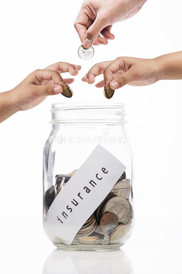 Hände, die eine Münze in Glasflasche, Investition für Versicherungskonzept setzen lizenzfreie stockfotografie