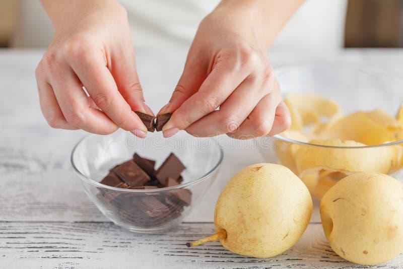 Hände, die eine Schokolade in der Schüssel brechen lizenzfreie stockfotos