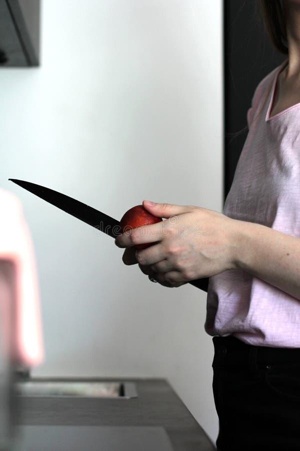 Hände, die einem Kochapfel auf einer Küche abziehen lizenzfreies stockfoto