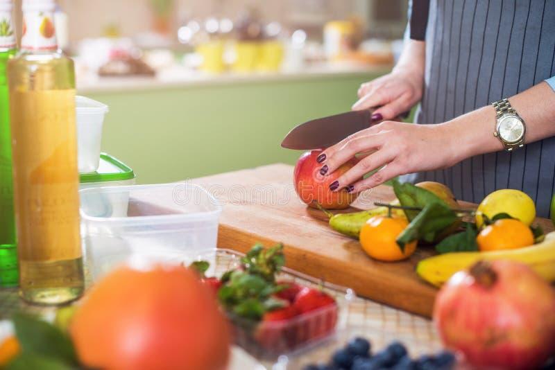 Hände, die einen Apfel auf hackendem Brett schneiden Junge Frau, die einen Obstsalat in ihrer Küche zubereitet stockbild