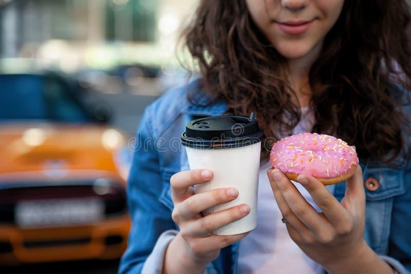 Hände, die einen Donut und einen Kaffee auf dem Hintergrund einer beschäftigten Metropole halten lizenzfreie stockfotos