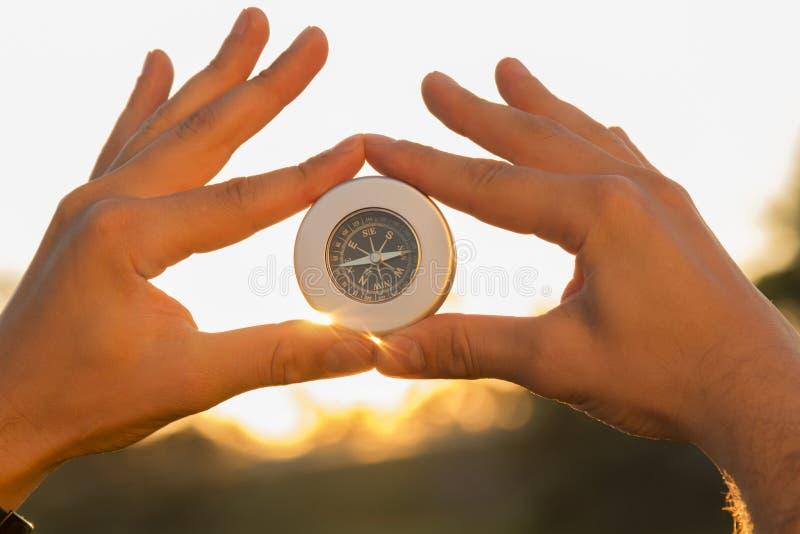 Hände, die einen Kompass bei Sonnenuntergang halten stockfotografie