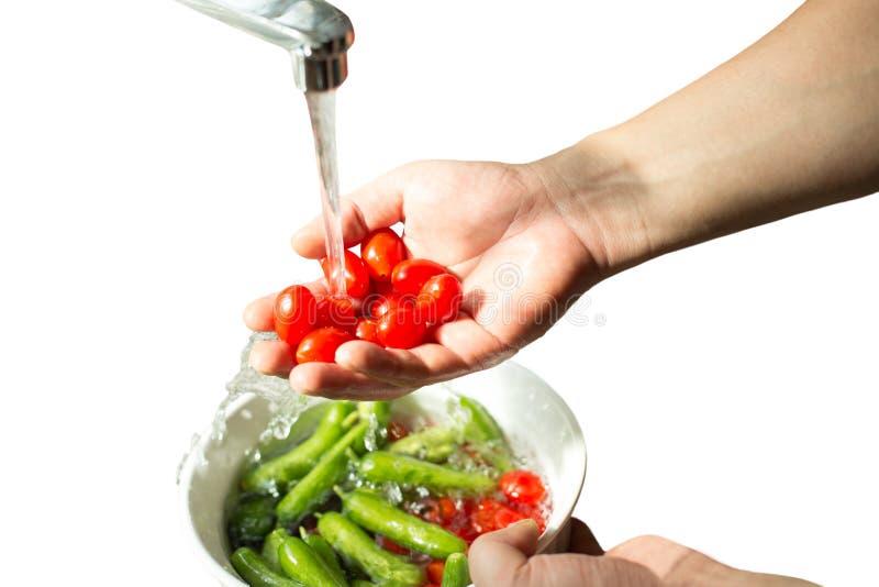 Hände, die frische Kirschtomaten im fließenden Wasser lokalisiert waschen lizenzfreie stockfotografie