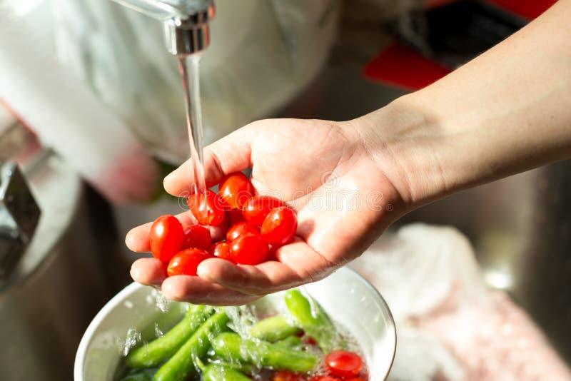 Hände, die frische Kirschtomaten im fließenden Wasser waschen lizenzfreies stockbild