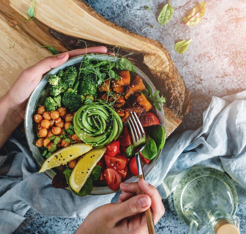 Hände, die gesundes superbowl oder Buddha-Schüssel mit Salat, gebackene Süßkartoffeln, Kichererbsen, Brokkoli, hummus, Avocado ha stockbilder