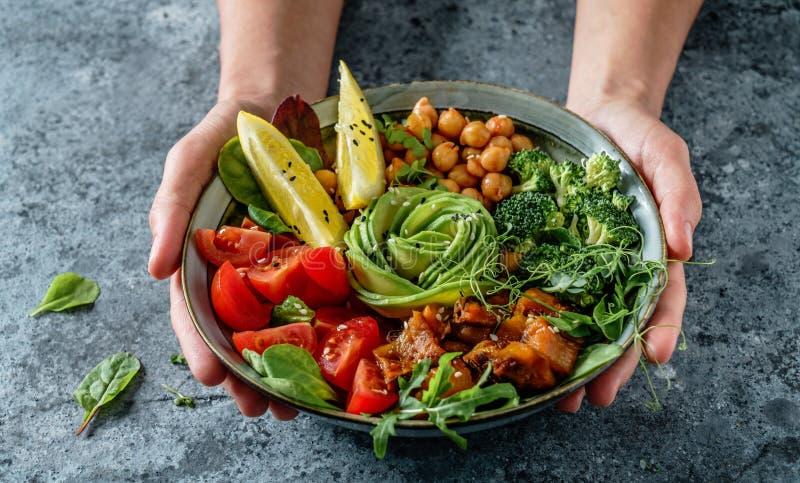 Hände, die gesundes superbowl oder Buddha-Schüssel mit Salat, gebackene Süßkartoffeln, Kichererbsen, Brokkoli, hummus, Avocado, S stockbild