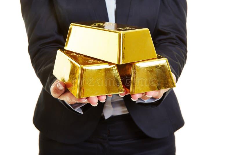 Hände, die Goldbarren halten stockbilder