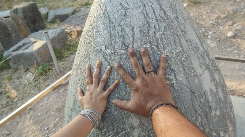 Hände, die heiligen Omphalos-Stein berühren lizenzfreies stockbild