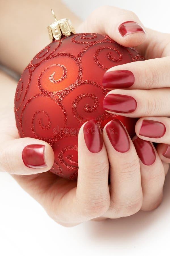 Hände, die kostbare rote Weihnachtskugel anhalten stockfotografie