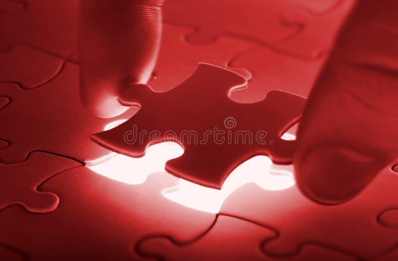 Hände, die letztes Stück eines Puzzlespiels platzieren stockfotos