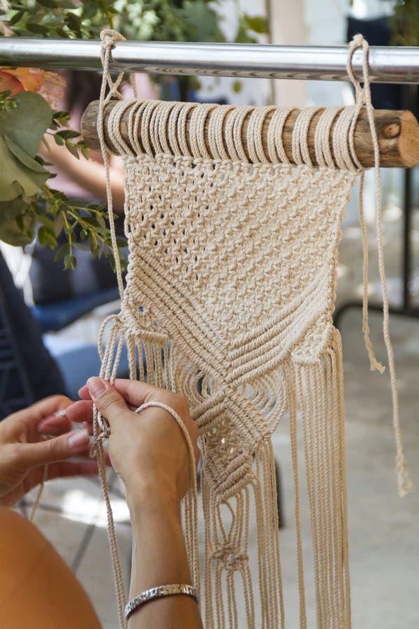 Hände, die Makrameetapisserie mit beige Faden spinnen stockfotos