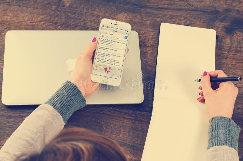 Hände, die Mobiltelefon und Stift auf Schreibtisch halten