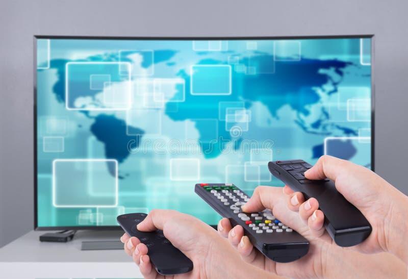 Hände, die Multimedia Fernsteuerungs mit intelligentem Fernsehen halten lizenzfreies stockfoto