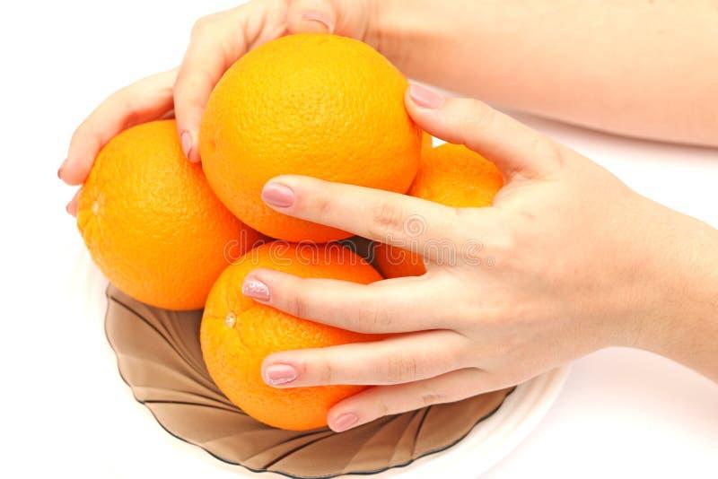 Hände, die Orangen halten stockbild