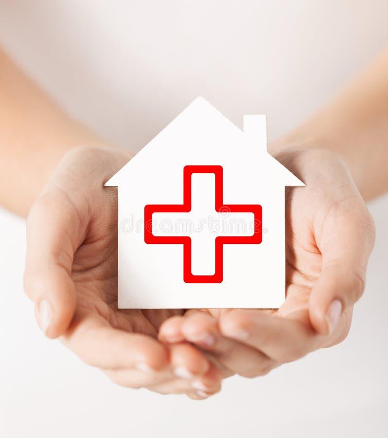 Hände, die Papierhaus mit rotem Kreuz halten lizenzfreie stockfotografie
