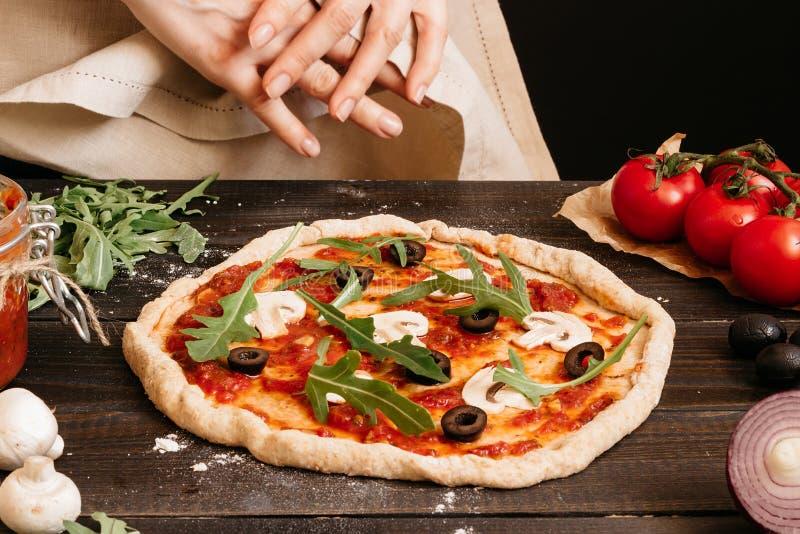 Hände, die Pizza in der Küche kochen Pizzabestandteile auf dem Holztisch stockfotografie