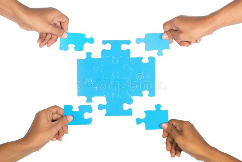 Hände, die Puzzlespiel zusammenbauen. lizenzfreie stockfotografie