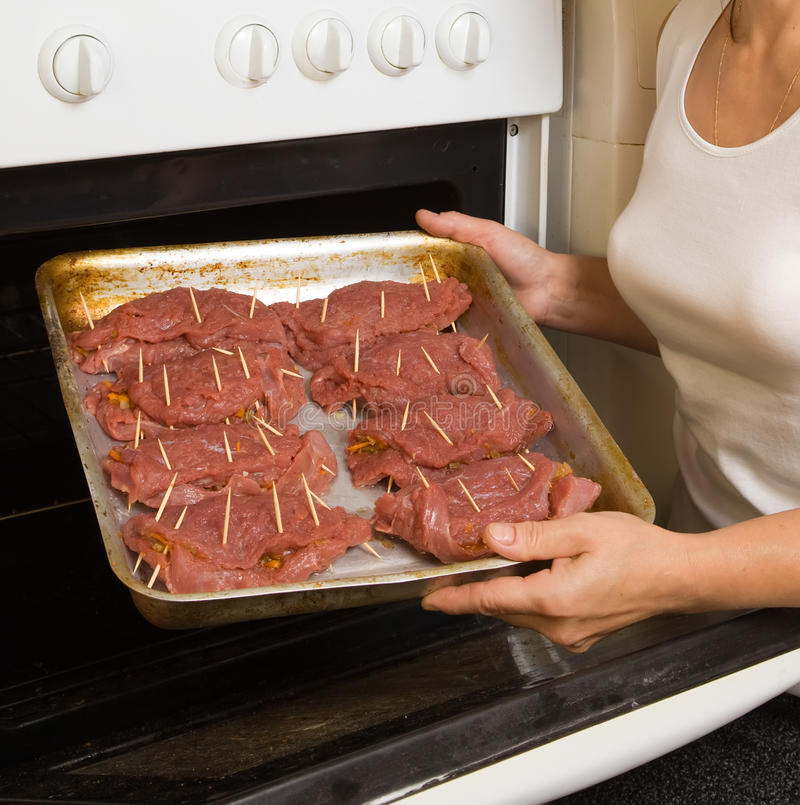 Hände, die Rindfleisch in ove setzen stockbilder
