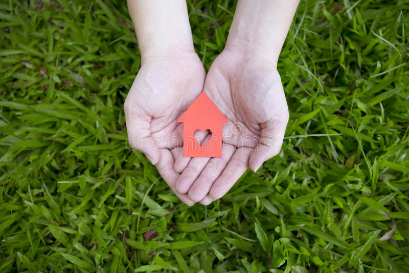Hände, die rotes Papierhaus halten stockbild