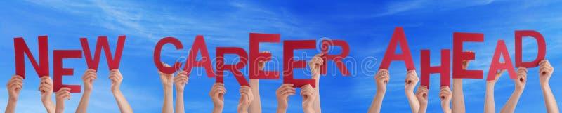 Hände, die rotes Wort-neuen Karriere-voran blauen Himmel halten stockbilder