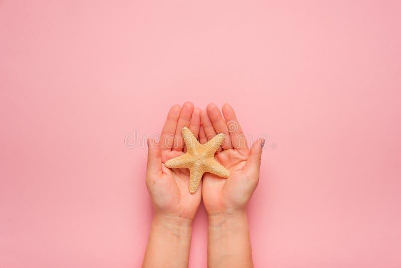 Hände, die Starfish halten Symbol des Sommers, Entspannung auf dem Strand Modischer Sommer lizenzfreie stockbilder